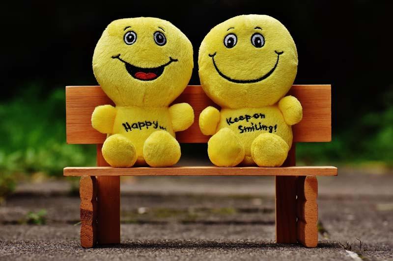 Dos sonrientes peluches sentados en un banco